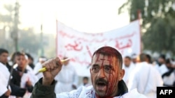 """Shi'ite Muslims perform """"tabrir"""" -- the cutting of the forehead -- during the culmination of the Ashura ceremonies in Baghdad."""