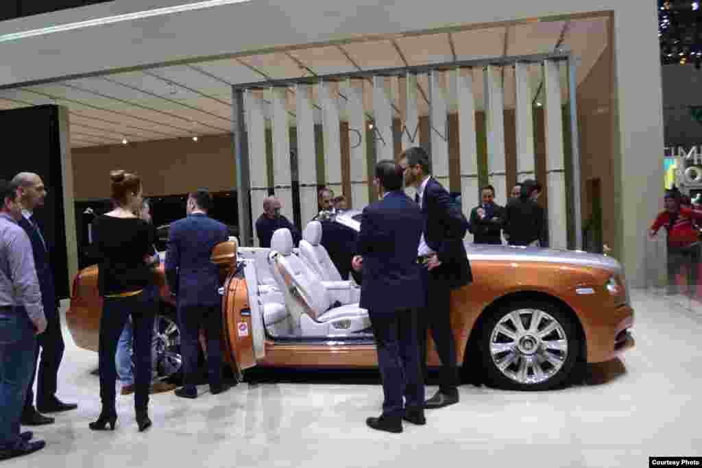 Около Rolls-Roys собрались состоятельные посетители автосалона.