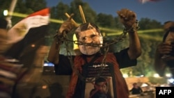 A man wearing a mask of ousted President Muhammad Morsi shows his handcuffed hands outside the presidential palace in Cairo on July 19, while Morsi opponents gather to mark the 40th anniversary of the Six-Day War against Israel.