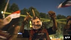 Čovek nosi masku sa likom zatvorenog egipatskog predsednika Mohameda Morsija