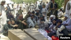 People gather around the coffins of men who were killed in the Kandahar attack.
