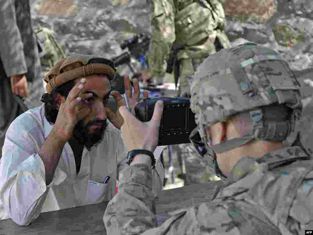 A U.S. Army soldier scans the eyes of an Afghan man for a biometric ID system near the border with Pakistan. (AFP PHOTO/Tauseef Mustafa)