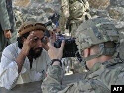 په تورخم کې یو امریکايي سرتېری د یوه افغان د سترګو عکس اخلي.