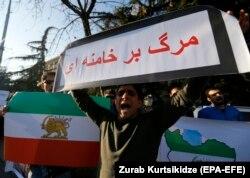 """Иранның Грузиядағы елшілігі алдында наразылыққа шыққан адамдар қолдарына """"Хаменеиге өлім келсін!"""" деген ұран мен Иранның шах дәуіріндегі туын алып шықты. Тбилиси, 4 қаңтар 2018 жыл."""