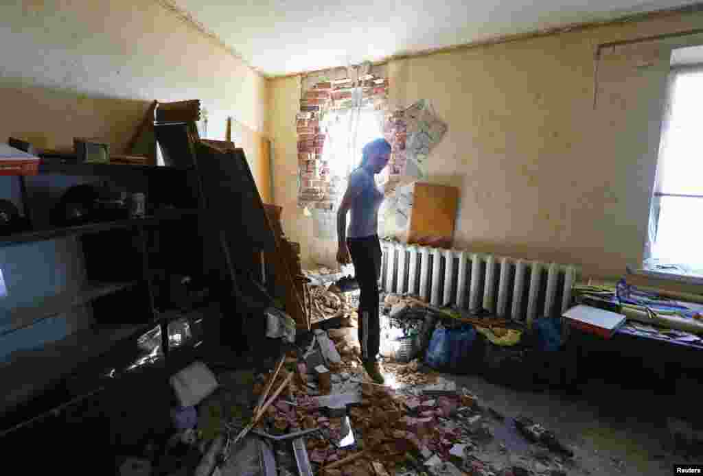 Local resident Tatyana Markova walks inside a house damaged by shelling in the eastern Ukrainian city of Slovyansk on July 1. (Reuters/Shamil Zhumatov)