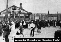 «Черга за хлібом на харківському базарі у 1933 році. На фронтоні закритого магазину, як знущання, малюнок соковитих фруктів, які тут продавалися» (авторський підпис). На фото: Благовіщенський базар (офіційна назва Центральний комунальний ринок) у центрі Харкова. На світлині можна побачити, як дерев'яні павільйони базару виглядають з-за фруктового і хлібного навісів. Під час Другої світової війни ринок був повністю зруйнований. Фото Александра Вінербергера, ілюстрація із книги «Hart auf hart. 15 Jahre Ingenieur in Sowjetrußland. Ein Tatsachenbericht, Salzburg 1939»