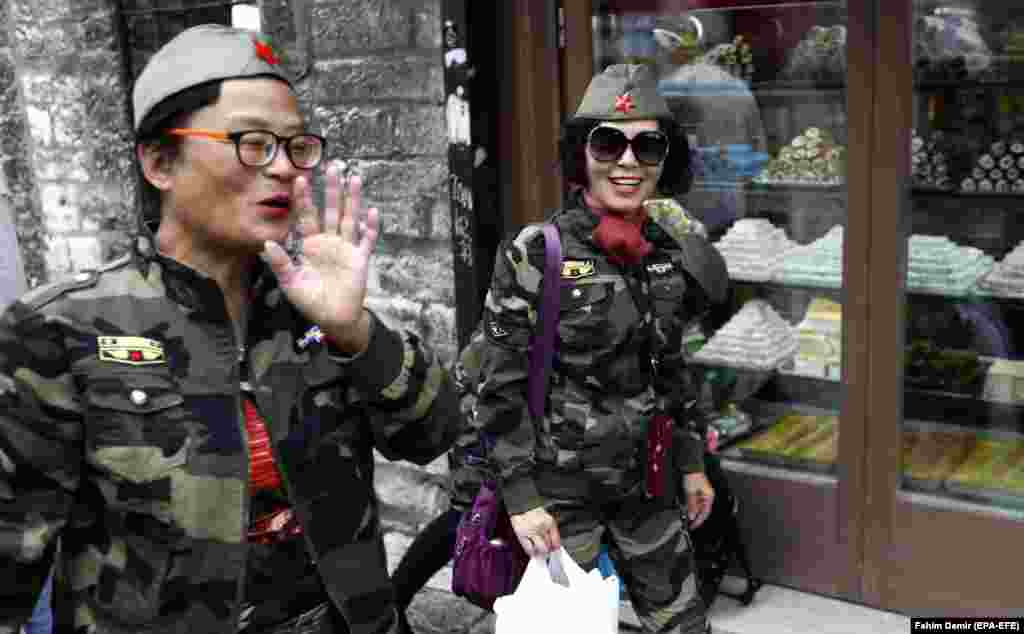 Chinese tourists dressed in military uniforms walk in the Bosnian capital, Sarajevo. (epa-EFE/Fehim Demir)