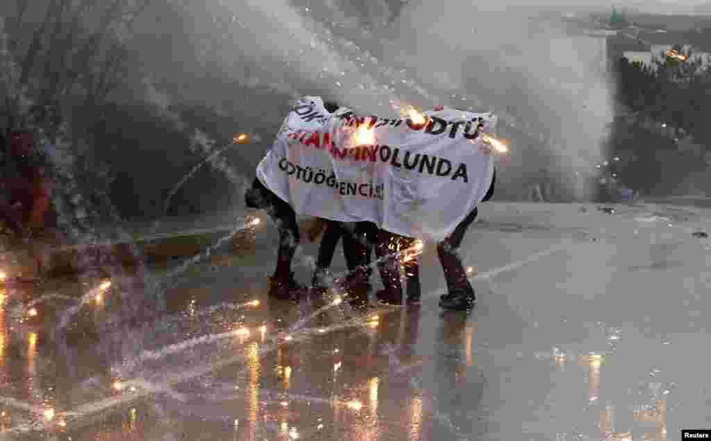 معترضان در آنکارا و پناه گرفتن در مقابل فشار آّب قوی از سوی نیروهای پلیس