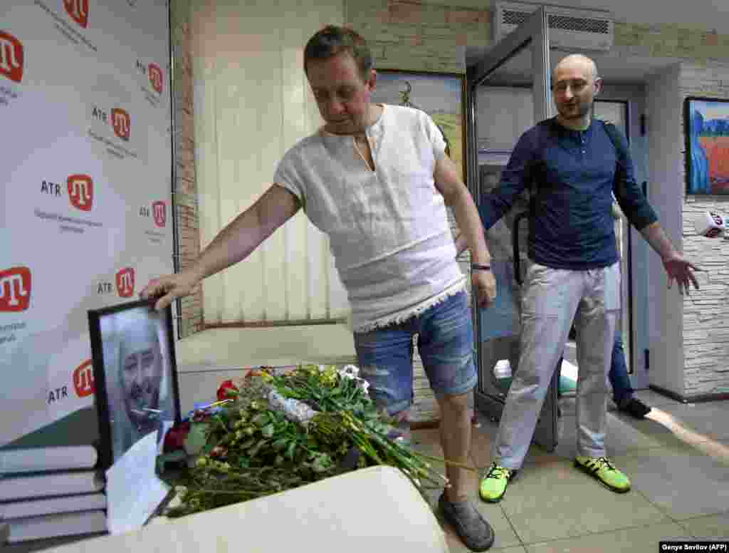 Russian dissident journalist Arkady Babchenko (right) and the deputy chief of the Crimean Tatar channel ATR where he works, Aider Muzhdabaiev, look at a memorial set up by Babchenko's colleagues after news of his death, in Kyiv on May 31. Babchenko's death was faked by Ukraine's security services to uncover what they said was a plot to assassinate him. (AFP/Genya Savilov)
