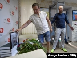 Babchenko (right) and the deputy chief of the Crimean Tatar channel ATR, Aider Muzhdabaiev, look at the memorial set up by Babchenko's colleagues after news of his death, in Kyiv on May 31.