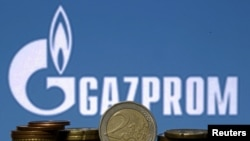 Euro coins are seen in front of displayed logo of Gazprom - generic