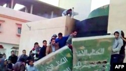 This video grab shows demonstrators destroying a monument to Muammar Qaddafi's Green book.