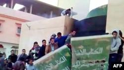 This video grab shows demonstrators destroying a monument to Muammar Qaddafi's Green book.