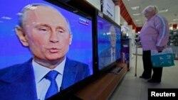 Кибеттәге бер ханым Путин чыгышын күзәтә