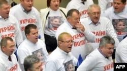 """Oppozisiýadaky deputatlar parlamentde bolan ses berişlikden soň """"Utanç!"""" diýip gygyrýarlar. Kiýew, 21-nji noýabr, 2013."""