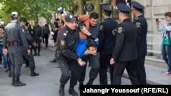 Полиция жастар ұйымының белсендісін ұстап жатыр. Әзербайжан, Баку, 6 мамыр 2014 жыл.