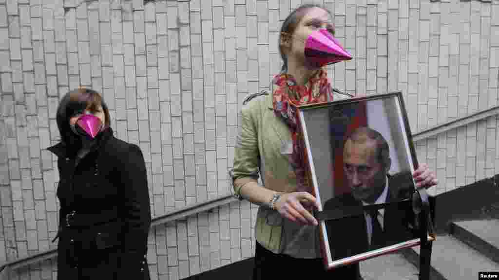 Russian opposition activists pose with a portrait of President Vladimir Putin, with a black ribbon commonly used for the deceased tied around it, on Putin's birthday in Moscow on October 7. (Reuters/Maksim Shemetov)