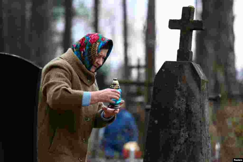 Женщина зажигает свечу на могиле усопшего родственника, Беларусь