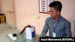 احد موظفي مفوضية الانتخابات وبجنبه جهازالختم الالكتروني