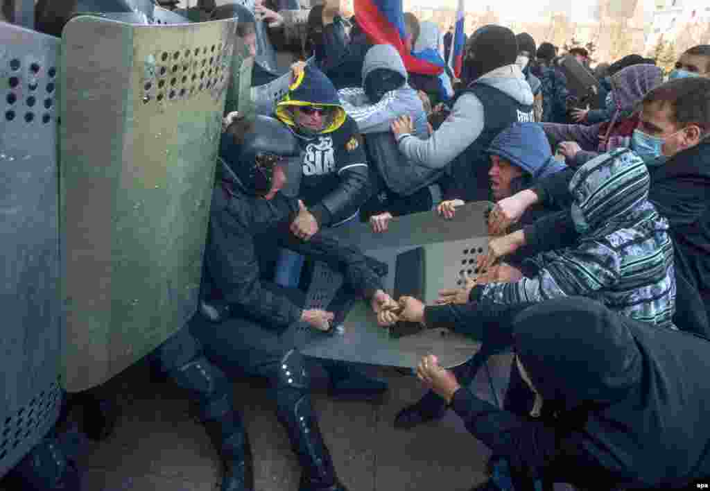 Pro-Russia protesters clash with police as they try to occupy a regional administration building in Donetsk.