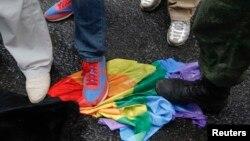 ЛГБТ қауымдастығы құқығын қорғаушылардың түрлі-түсті жалауын таптап жатқан гейлерге қарсы белсенділер. (Көрнекі сурет.)