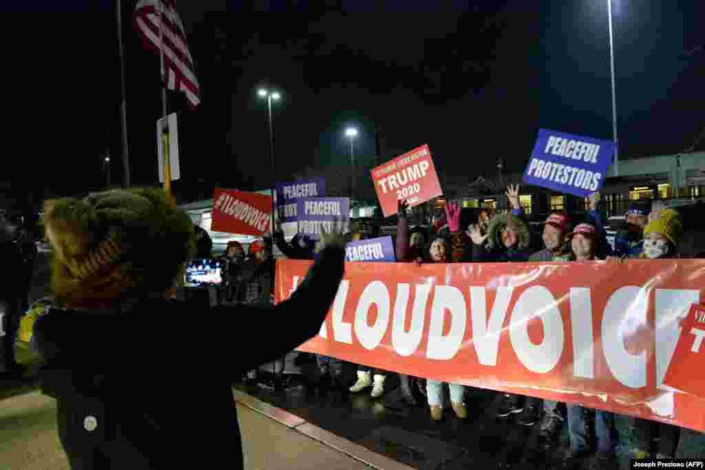 Прихильники президента США Дональда Трампа тримають плакати і скандують гасла, очікуючи прибуття автобусів, які доставлять їх до Вашингтона, округ Колумбія. Ньютон, штат Массачусетс. 5 січня 2021 року