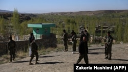Afghan security personnel guard the site of an attack by Taliban militants on a government compound in Ghazni Province on April 12.