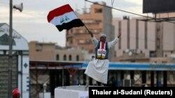 Майрамдык салтанат учурунда Багдаддагы Тахрир аянтында Ирактын желегин кармап турган адам. 10-декабрь, 2017-жыл.