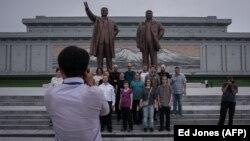 Пхеньянның орталық алаңында Солтүстік Корея көсемдерінің ескерткіші жанында суретке түсіп жатқан туристер (Көрнекі сурет).