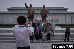 Туристи позують на тлі статуй північнокорейських політичних лідерів, Пхеньян