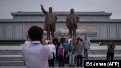 Туристы на фоне статуй великих руководителей