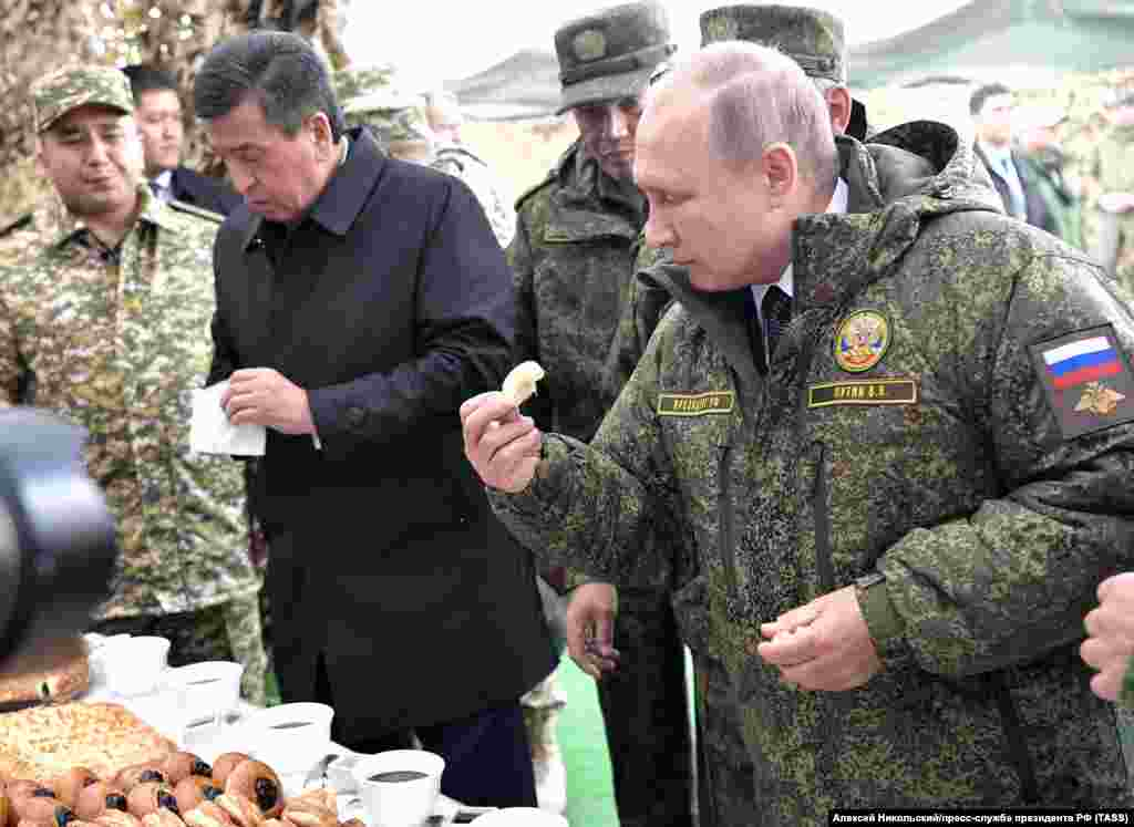 Kyrgyz President Sooronbai Jeenbekov (left) and Vladimir Putin grab a bite to eat after observing the maneuvers. Jeenbenkov was the only foreign leader to attend the exercises.