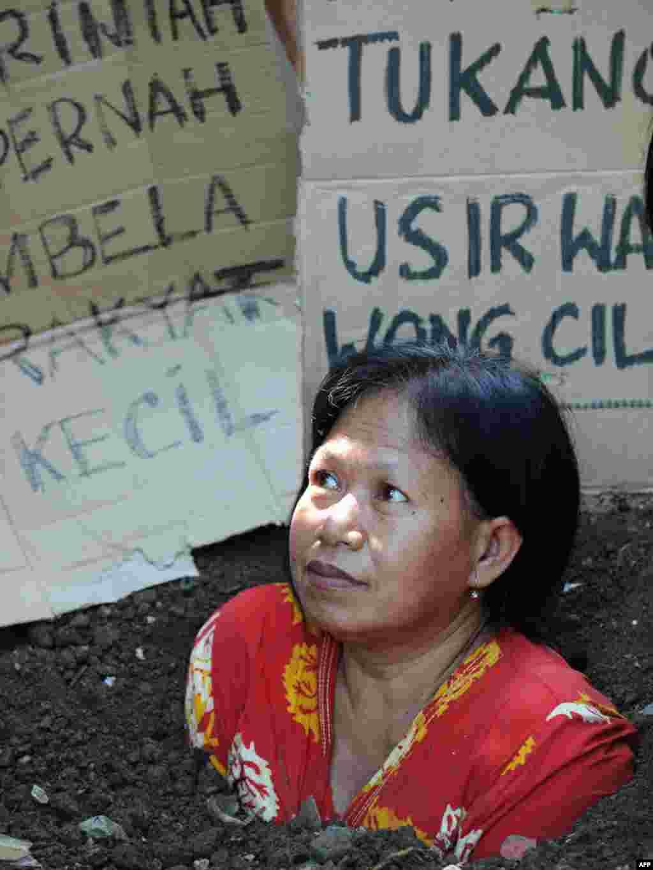 Інданэзія: жыхарка Джакарты закапалася ў зямлю на знак пратэсту супраць яе высяленьня дзеля будаўніцтва офісаў
