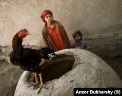 Village children with a rooster standing atop a traditional mud oven used for baking flatbread
