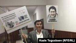 Мырзахан Еримбетов в здании Алматинского городского суда с плакатами, которые он использовал 10 мая 2018 года в акции протеста против пыток в отношении его сына 47-летнего предпринимателя Искандера Еримбетова. Алматы, 5 июня 2018 года. (Фото предоставлено Мырзаханом Еримбетовым).