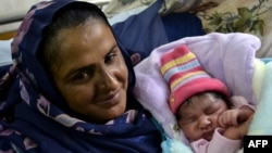 Mukhtar Mai shows off her newborn baby boy at a hospital in Multan in November 2011.