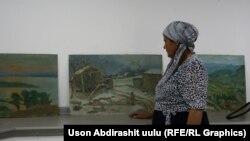Хадича Аскарова күйөөсү Азимжан Аскаров тарткан сүрөттөрдүн жанында турат. Атайын көргөзмө өтүп жаткан учур.