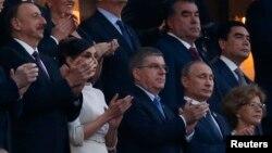 Ձախից՝ աջ. Ադրբեջանի նախագահ Իլհամ Ալիևը՝ կնոջ հետ, Միջազգային օլիմպիական կոմիտեի նախագահ Թոմաս Բախը, Ռուսաստանի նախագահ Վլադիմիր Պուտինը Եվրոպական խաղերի բացման արարողության ժամանակ, Բաքու, 12-ը հունիսի, 2015 թ․