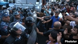 Protesters scuffle with riot police near a police station seized by opposition gunmen in Yerevan on July 19.