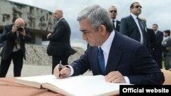 Հայաստան նախագահը գրառում է կատարում Մայդանեկ թանգարանային համալիրի պատվավոր հյուրերի գրքում, 26-ը հունիսի, 2013թ.