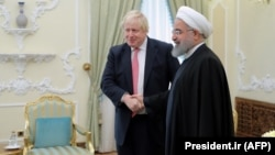 Iranian President Hassan Rohani (right) meets with British Foreign Secretary Boris Johnson in Tehran on December 10.