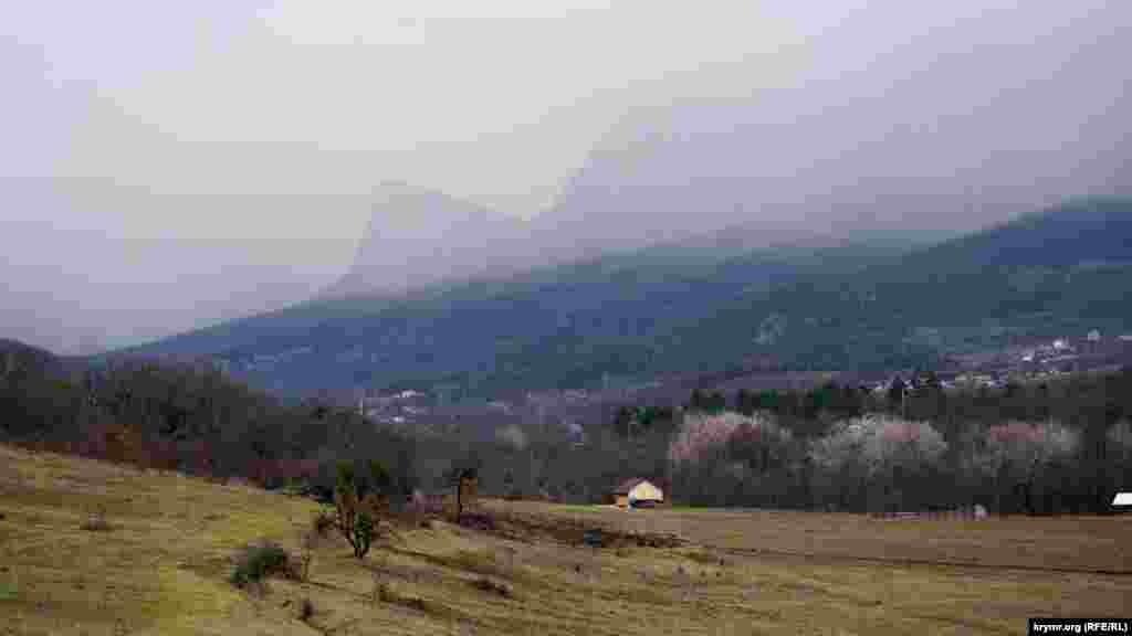 Дрібний дощ на тлі Головної гряди Кримських гір. Майже в центрі – затуманена гора Орлиний Заліт (Седам-Кая). Ліворуч видніються будівлі села Соколине Бахчисарайського району