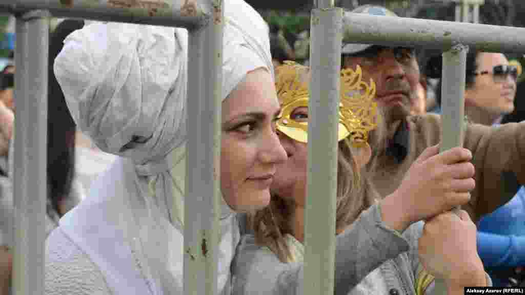 Женщина в необычном головном уборе с дочерью в маске среди зрителей фестиваля.