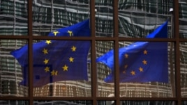 Belgium -- A European flag reflects in a building of the EU headquarters in Brussels, 06Nov2007