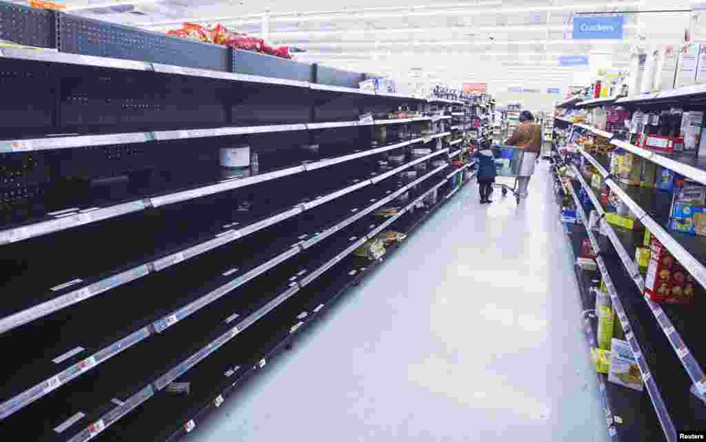 A woman and child walk through an aisle, emptied in preparation for Hurricane Sandy, in a Wal-Mart store in Riverhead, New York.
