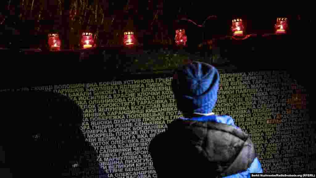 Хлопчик стоїть біля назв сіл і містечок, які постраждали від Голодомору. Під час голоду 1932–1933 років в Україні вимерли десятки сіл, сотні на десятиріччя обезлюднились