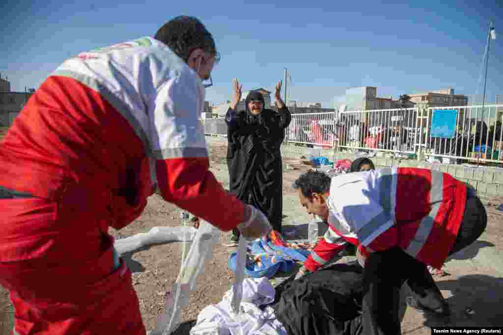 A woman reacts as medics cover dead bodies in Sarpol-e Zahab.
