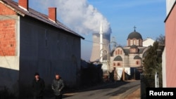 Men walk along the street in front of an Orthodox Church and a mosque as smoke billows out of the towers of a coal-fired power plant in Obilic, near Pristina, on December 5.