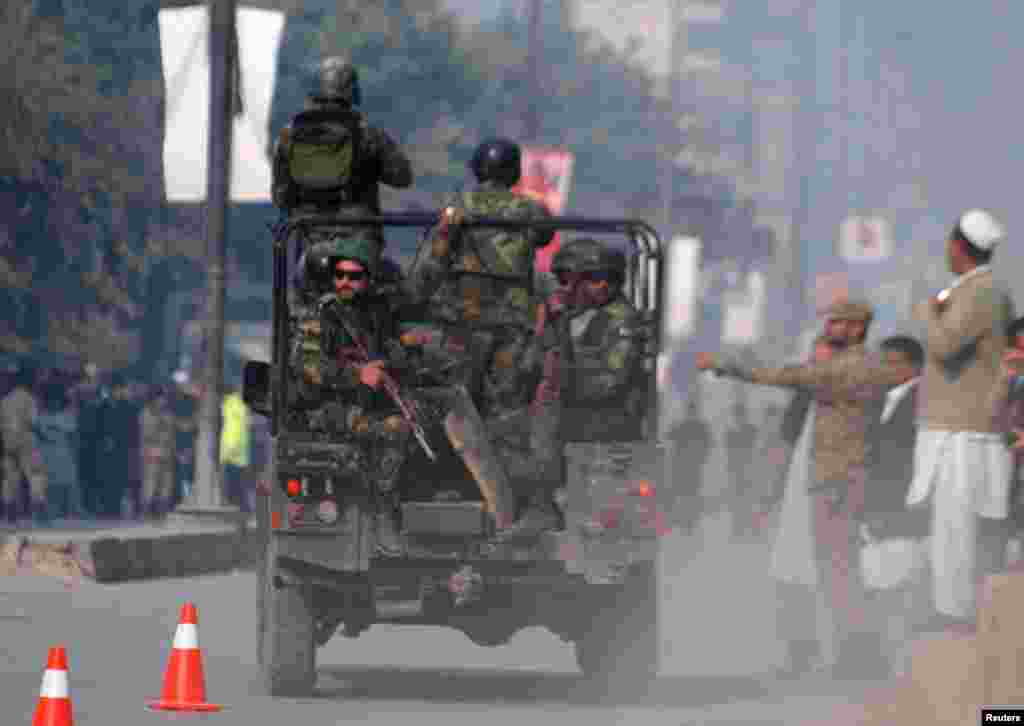 Pakistani security forces drive on a road leading to the Army Public School that came under attack by Taliban gunmen in Peshawar.