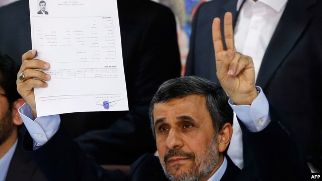 Former Iranian President Mahmud Ahmadinejad flashes the victory sign at the Interior Ministry's election headquarters after registering to run for president.